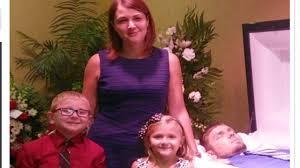 Redes sociales enfurecen porque una mujer posó sonriente con sus hijos junto al féretro de exesposo drogadicto
