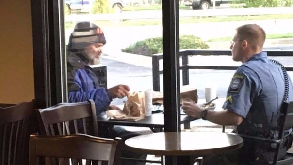 Policía pasa su hora de almuerzo con un indigente en mesa de restaurante